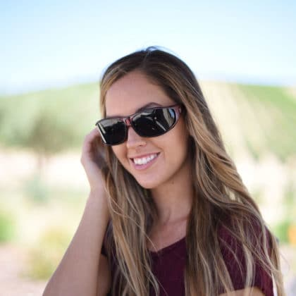 Jory Paul wears burgundy Vistana fit over sunglasses with gray polarized lenses to shield her eyes from solar radiation.