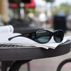 polarized fitover sunglasses sitting on a newspaper