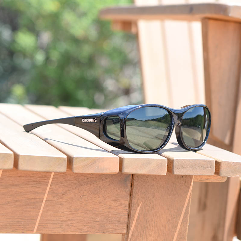 8065a30f1257 Black fitover sunglasses on deck chair