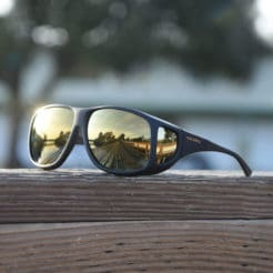 Cocoons fitover sunglasses on wooden railing with gold mirror