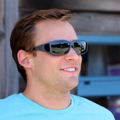 Man wears slate gray sunglasses designed to fit over regular eyeglasses.